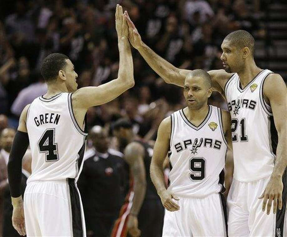 San Antonio Spurs' Danny Green (4), Tony Parker (9) and Tim Duncan (21) react against the Miami Heat during the second half at Game 5 of the NBA Finals basketball series, Sunday, June 16, 2013, in San Antonio. (AP Photo/Eric Gay) Photo: AP / AP