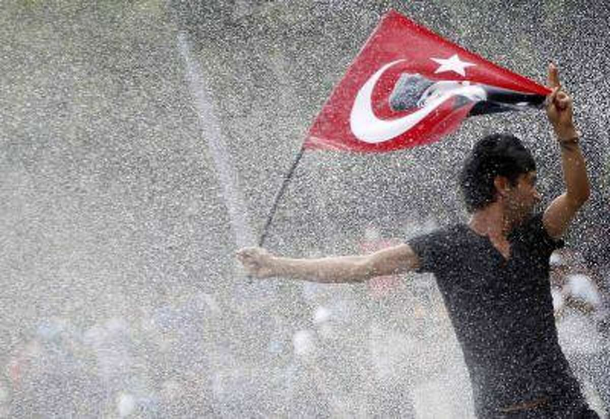 A protester is attacked by water cannon during crowds in Kizilay square in central Ankara, June 16, 2013.