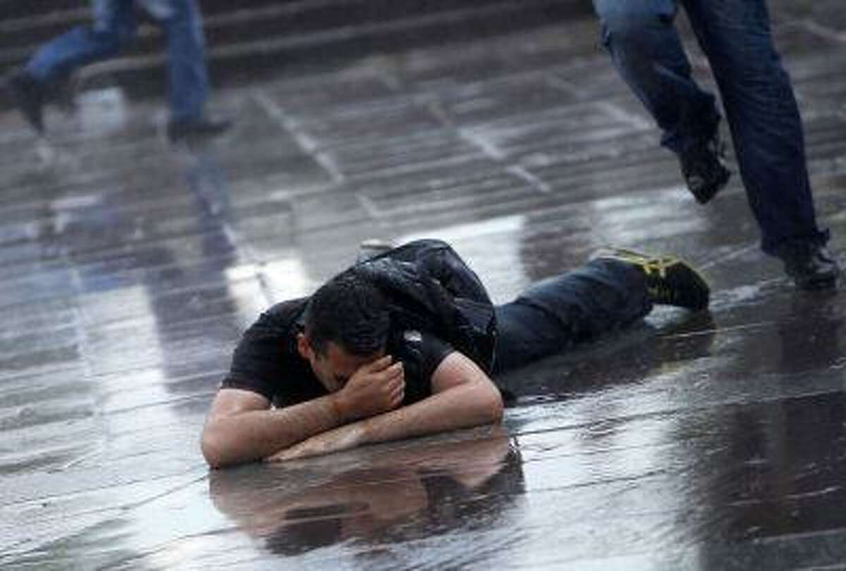 A man lies on the ground after being hit by a water cannon during a protest in Kizilay square, central Ankara June 16, 2013.