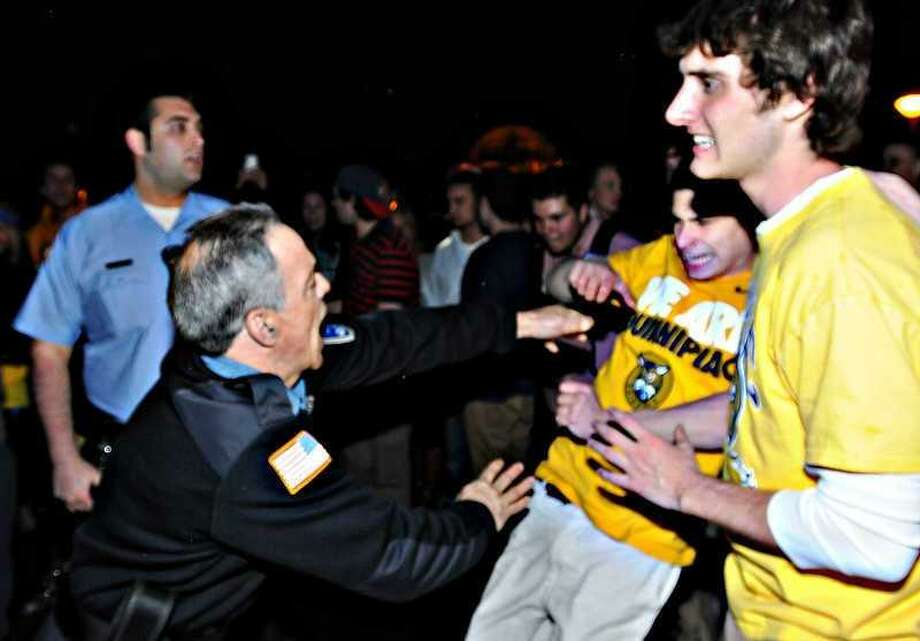 A security officer and a Quinnipiac University student have an altercation as Quinnipiac University students gather on the Hamden campus after  Yale University defeated Quinnipiac 4-0 during the  Frozen Four NCAA Division 1 Hockey Championship Game Saturday night April 13, 2013 .  Photo by Peter Hvizdak / New Haven Register