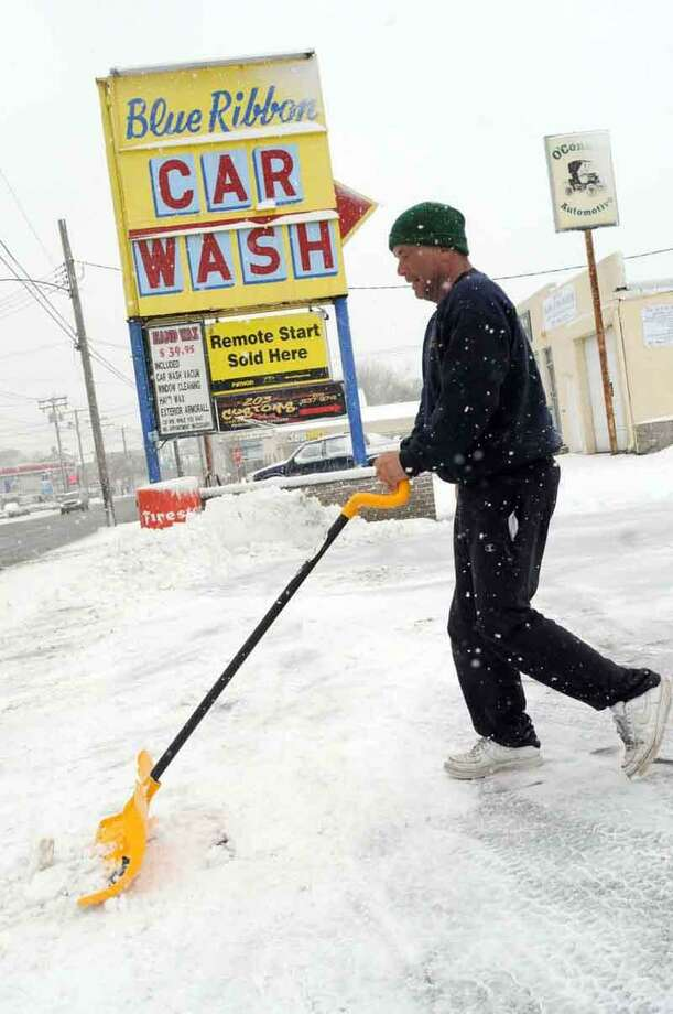 Terry Stone, a Blue Ribbon Car Wash employee, shovels snow from the front of the Elm Street car wash Friday, February 8, 2013 in West Haven. Stone says that once the snow stops the car wash business will be booming.  Connecticut.Blizzard warnings have been issued for all of Connecticut, according to the National Weather Service. Connecticut residents should brace for a possible blizzard Friday and into Saturday that could dump up to two feet of snow, along with high winds and the potential for coastal flooding.  Friday, February 8,  2013. Photo by Peter Hvizdak / New Haven Register Photo: New Haven Register / ©Peter Hvizdak /  New Haven Register