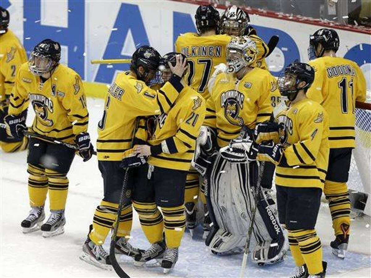 The Quinnipiac men's hockey team gather around goalie Eric Hartzell, top rear right, after losing to Yale 4-0 in the NCAA men's college hockey national championship game in Pittsburgh Saturday, April 13, 2013. (AP Photo/Gene Puskar)