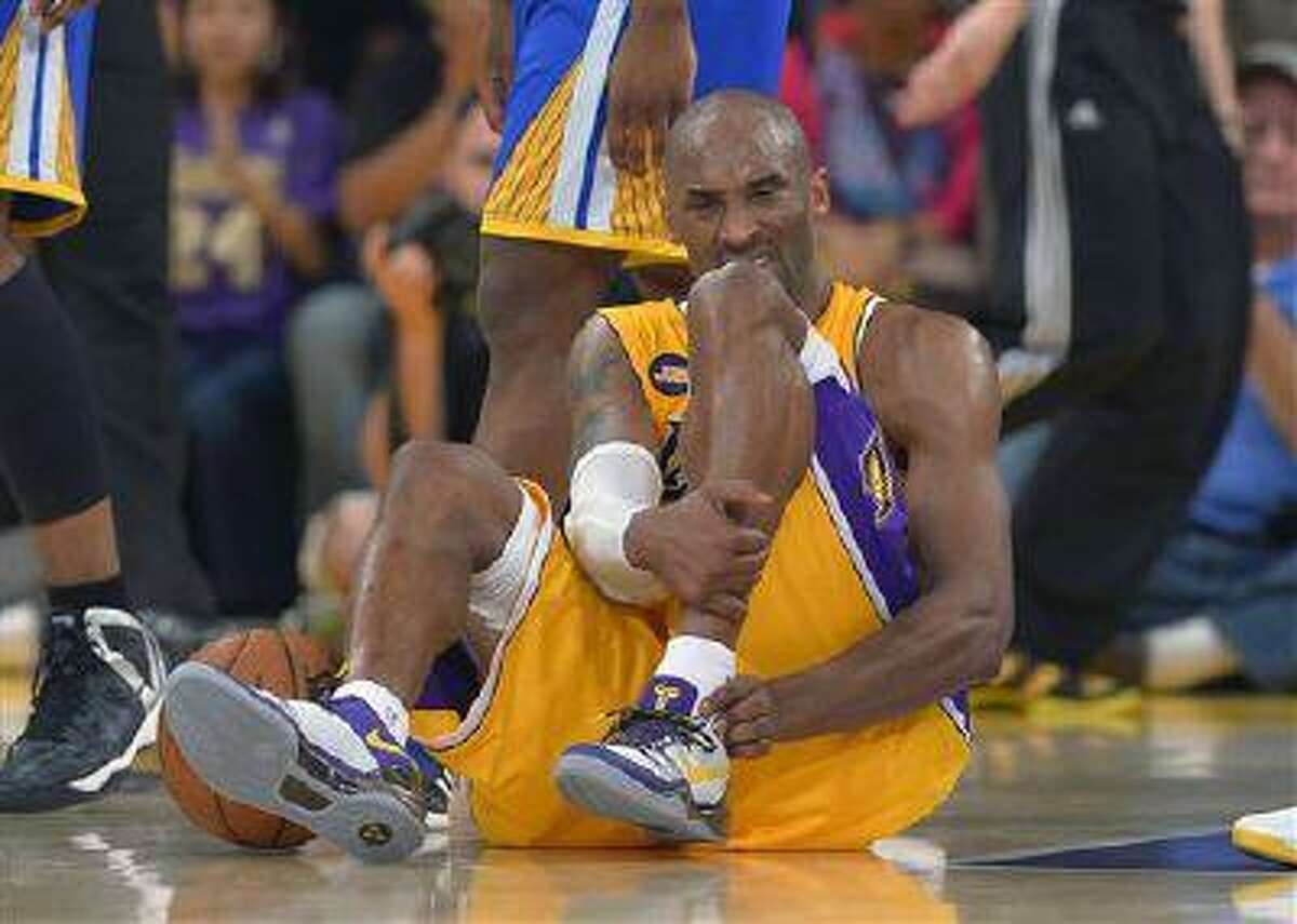 Los Angeles Lakers guard Kobe Bryant grimaces after being injured during the second half of a game against the Golden State Warriors, April 12, 2013, in Los Angeles.