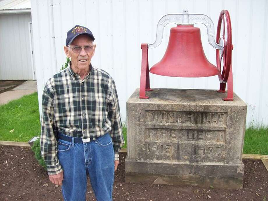 Photo by Mike Jaquays Firefighter Donald Dymes of Munnsville poses with the original circa 1916 fire alarm bell once used by the Munnsville Volunteer Fire Department at their station on June 14, 2013. The department celebrates their 100th anniversary this year, and will also host a Father's Day chicken barbecue at their South Main Street location today at noon.