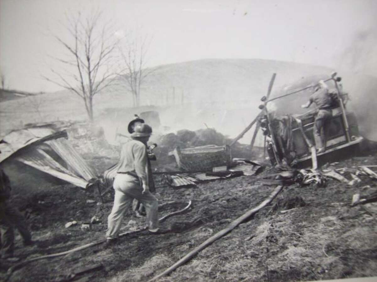 Photo from the Munnsville Fire Department Archives Munnsville Volunteer Fire Department members struggle in vain to free their truck from mud as the flames of a grass fire spread dangerously close on Streeter Road in the village on March 29, 1962.
