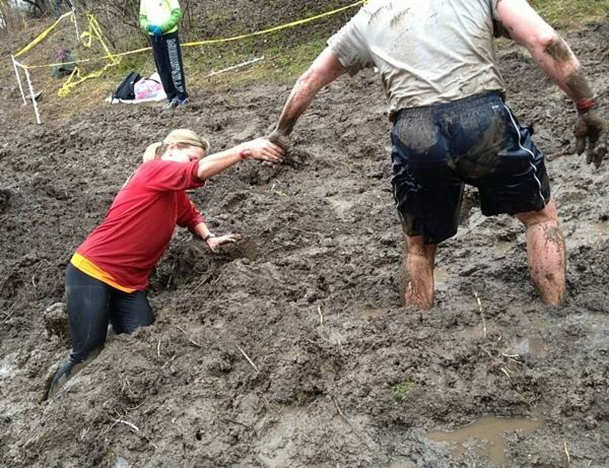 PHOTO BY JOHN HAEGER @ ONEIDAPHOTO ON TWITTER/ONEIDA DAILY DISPATCH After crawling the pipe Suzanna Price of West Winfield NY, gets a helping hand from Robert Mortensen of King Park Long Island as she makes her way through knee deep mud during the Daniel Barden Highland Mudfest on Saturday, April 13, 2013 in Deansboro. Price was the first women to cross the finish line.