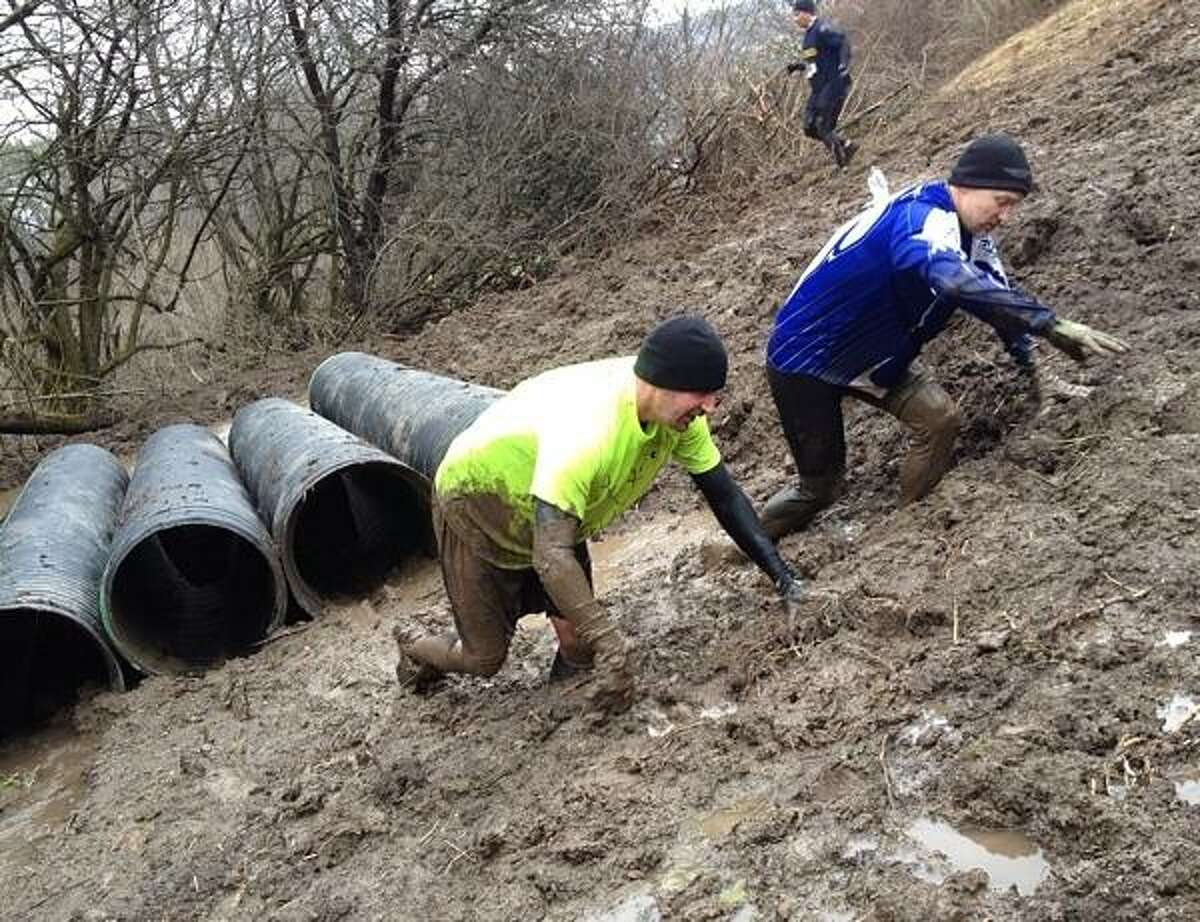 PHOTO BY JOHN HAEGER @ ONEIDAPHOTO ON TWITTER/ONEIDA DAILY DISPATCH After crawling the pipes runners makes their way through knee deep mud during the Daniel Barden Highland Mudfest on Saturday, April 13, 2013 in Deansboro.