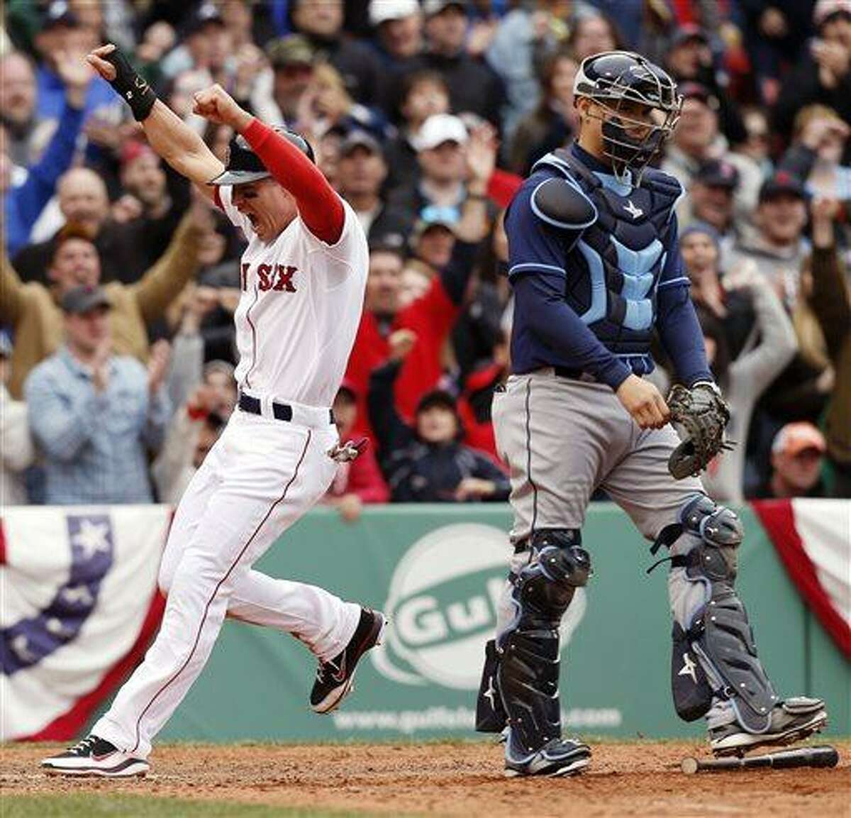 Boston Red Sox's Jacoby Ellsbury, left, celebrates behind Tampa Bay Rays' Jose Lobaton as he scores the game-winning run on an RBI single by teammate Shane Victorino in the 10th inning of a baseball game in Boston, Saturday, April 13, 2013. The Red Sox won 2-1. (AP Photo/Michael Dwyer)