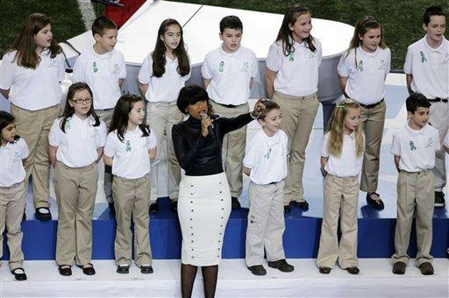 """FILE - In this  Feb. 3, 2013 file photo, Jennifer Hudson performs with students from Sandy Hook Elementary School singing """"America the Beautiful"""" before the NFL Super Bowl XLVII football game between the San Francisco 49ers and the Baltimore Ravens in New Orleans.  In the weeks since the school shooting, the music world has helped the town come together and heal. (AP Photo/Gerald Herbert, File) Photo: AP / AP"""