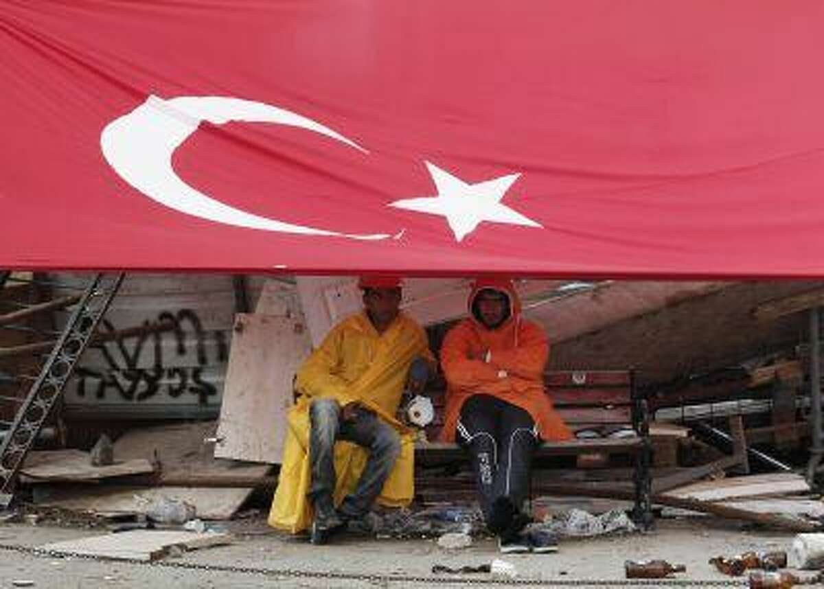 Protesters sit in front of the barricade in Istanbul's Taksim Square June 15, 2013.
