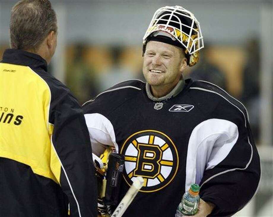 Boston Bruins goalie Tim Thomas smiles as he talks with coach Bob Essensa, left, during a session of their hockey training camp at the Waterbury Ice Center in Waterbury, Vt., Friday, Sept. 28, 2007. The Bruins are spending two days training in Vermont following their loss in Montreal on Thursday. (AP Photo/Toby Talbot) Photo: ASSOCIATED PRESS / AP2007