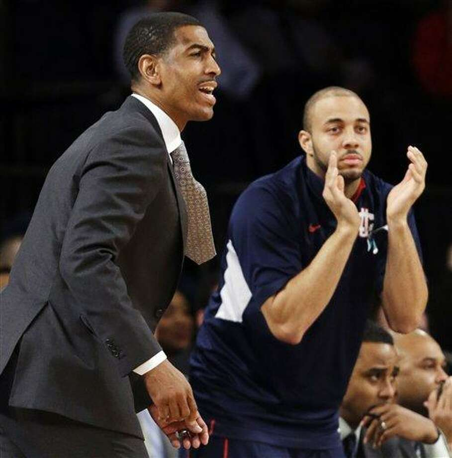 Connecticut head coach Kevin Ollie, left, reacts in the first half of their NCAA college basketball game against St. John's at Madison Square Garden in New York, Wednesday, Feb. 6, 2013. St. John's won 71-65. (AP Photo/Kathy Willens) Photo: AP / AP