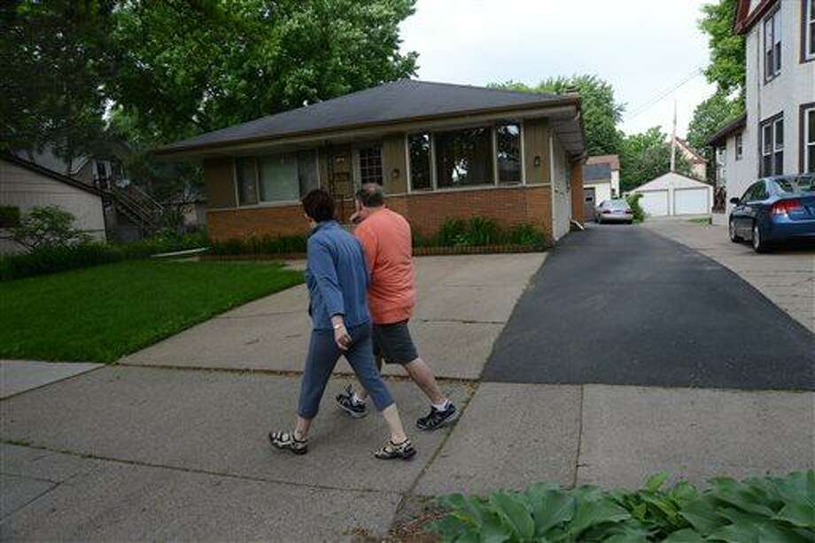 People walk past the home in Minneapolis, Minn., where 94-year-old Michael Karkoc lives, Friday, June 14, 2013.  Karkoc, a top commander of a Nazi SS-led unit accused of burning villages filled with women and children, lied to American immigration officials to get into the United States and has been living in Minnesota since shortly after World War II, according to evidence uncovered by The Associated Press. He told American authorities in 1949 that he had performed no military service during World War II, concealing his work as an officer and founding member of the SS-led Ukrainian Self Defense Legion and later as an officer in the SS Galician Division, according to records obtained by the AP through a Freedom of Information Act request. (AP Photo/The Star Tribune, Richard Sennott)  MANDATORY CREDIT; ST. PAUL PIONEER PRESS OUT; MAGS OUT; TWIN CITIES TV OUT Photo: AP / The Star Tribune