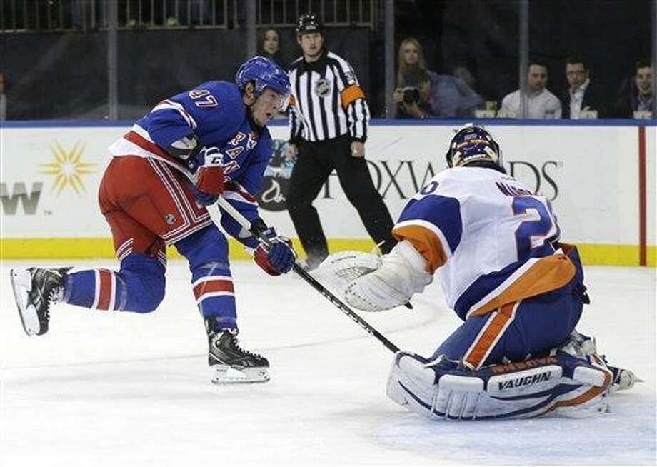 New York Rangers' J.T. Miller, left, scores a goal past New York Islanders goalie Evgeni Nabokov, right, during the second period of the NHL hockey game in New York, Thursday, Feb. 7, 2013.  (AP Photo/Seth Wenig) Photo: AP / AP