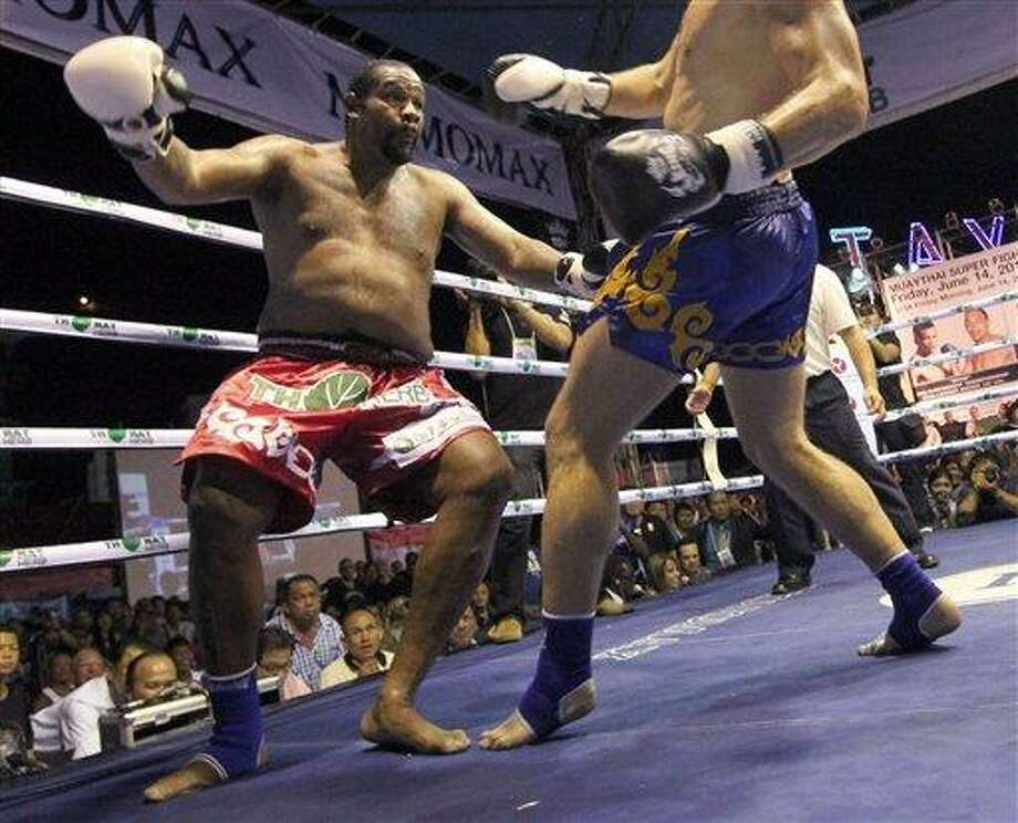 Former heavyweight boxing champion Riddick Bowe of the U.S., left, looses his balance after getting a kick from Levgen Golovin of Russia, right, during their WBC & WMC Muay Thai or Kick Boxing Super Heavyweight Championships fight in Pattaya, Thailand Friday, June 14, 2013. Golovin won the fight in a second round knockout. (AP Photo/Apichart Weerawong) Photo: AP / AP