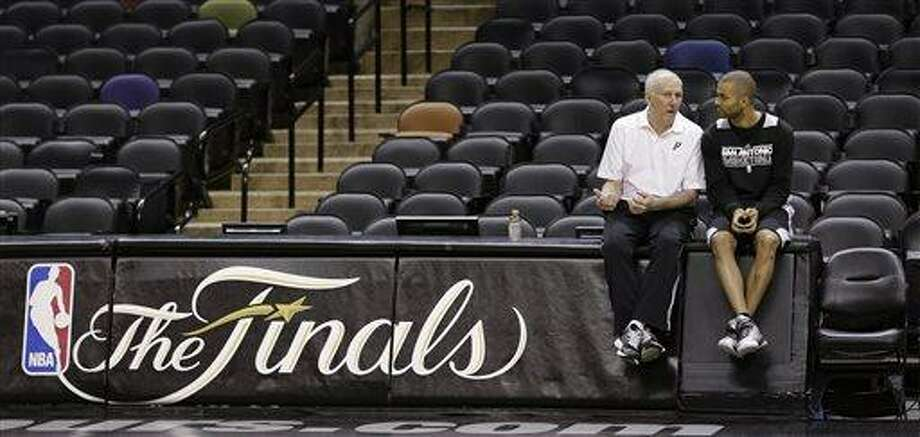 San Antonio Spurs head coach Gregg Popovich, left, and guard Tony Parker, right, of France, talks during a practice, Wednesday, June 12, 2013, in San Antonio. San Antonio will face the Miami Heat in game 4 of the NBA Finals basketball game Thursday. San Antonio leads the best-of-seven series 2-1.   (AP Photo/Eric Gay) Photo: AP / AP