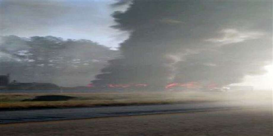 In this image made from video and provided by 13WMAZ TV, black smoke rises above a fiery crash on Interstate 16 near Montrose, Ga., about 40 miles southeast of Macon, Wednesday, Feb. 6, 2013, after several vehicles collided, killing at least three people. The crash shut down a roughly seven-mile stretch of the highway, forcing cars to be detoured around the area. (AP Photo/13WMAZ TV) Photo: AP / 13WMAZ TV