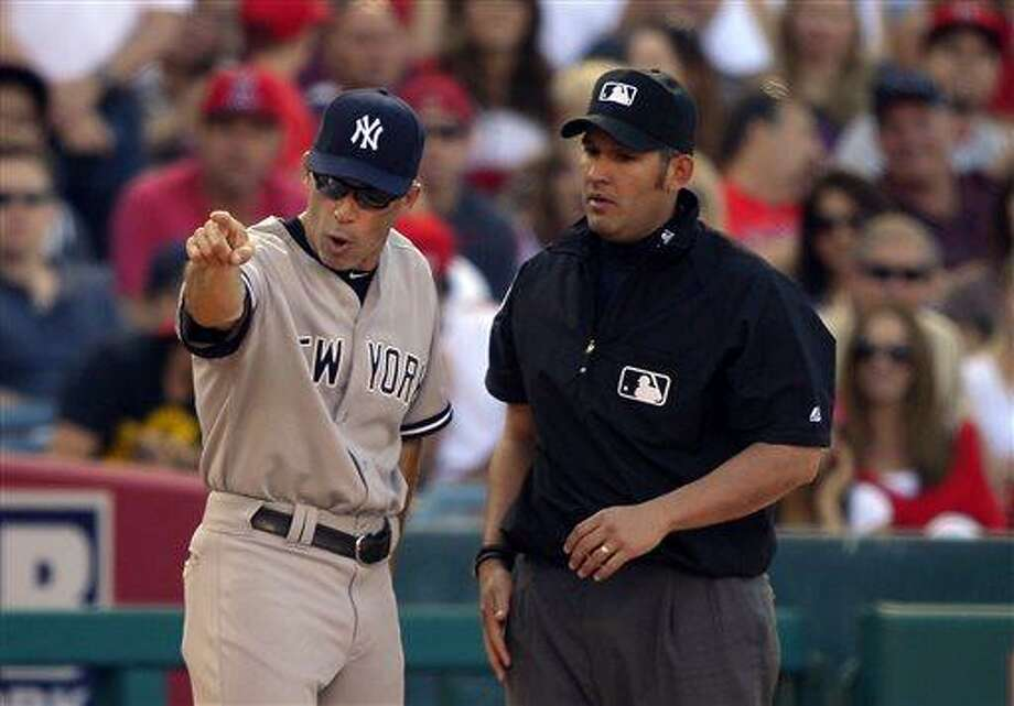 New York Yankees manager Joe Girardi, left, argues with third base umpire Manny Gonzalez after Yankees' Ichiro Suzuki was tagged out at third while trying to steal during the fourth inning of a baseball game against the Los Angeles Angels, Saturday, June 15, 2013, in Anaheim, Calif.  (AP Photo/Mark J. Terrill) Photo: AP / AP