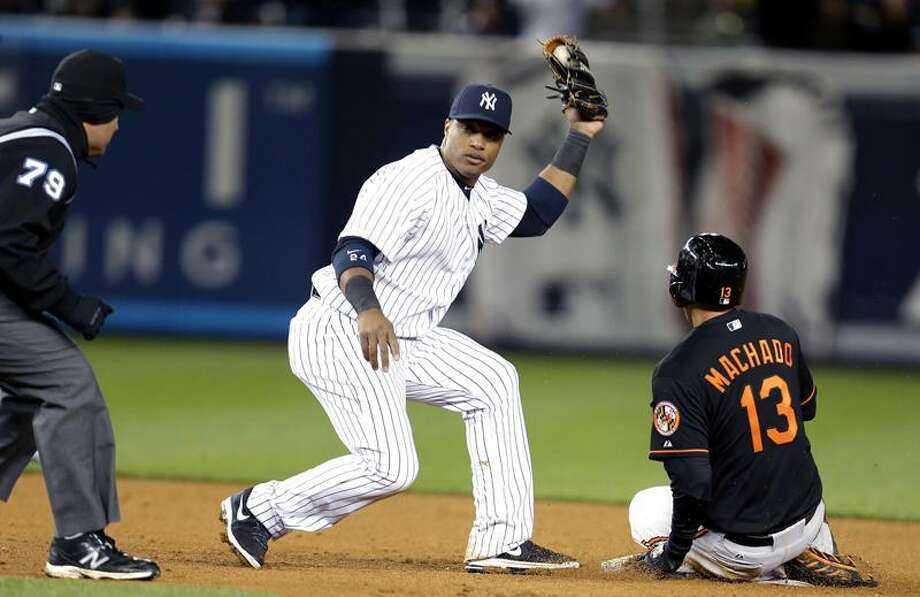 New York Yankees second baseman Robinson Cano, center, waits for the call from second base umpire Manny Gonzalez, left, after tagging Baltimore Orioles' Manny Machado for the third out of a triple play during the eight inning of a baseball game at Yankee Stadium in New York, Friday, April 12, 2013. (AP Photo/Julio Cortez) Photo: AP / AP2013