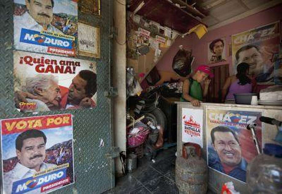 A boy stands inside his family's food stand, adorned with campaign election posters supporting the ruling party candidate, acting President Nicolas Maduro and former Presiden Hugo Chavez, in Caracas, Venezuela, April 12. Photo: AP / AP