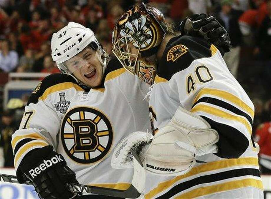 Boston Bruins defenseman Torey Krug (47) celebrates with goalie Tuukka Rask (40) after the Bruins scored a goal against the Chicago Blackhawks in sudden death overtime during Game 2 of the NHL hockey Stanley Cup Finals, Saturday, June 15, 2013, in Chicago. The Bruins won 2-1. (AP Photo/Nam Y. Huh) Photo: AP / AP