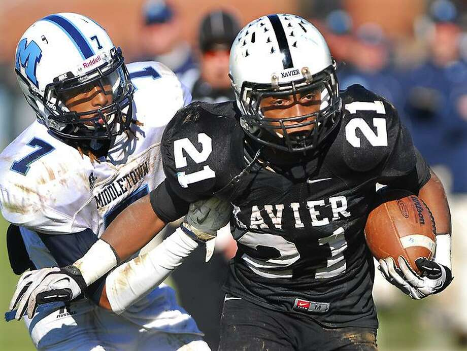 Catherine Avalone/The Middletown Press Xavier senior running back DeAngelo Berry tries to bring down Middletown's Isaiah Swain during the fourteenth annual Thanksgiving Day game at Corwin Stadium at Wesleyan University Thursday morning. Xavier won, 41-14. The athletic directors at Middletown High and Xavier announced Thursday the teams would not continue to play on Thanksgiving, ending the 15-game series.