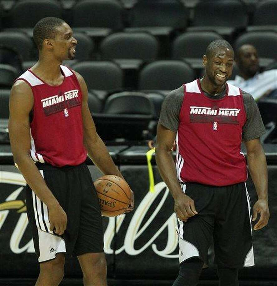 Miami Heat forward Chris Bosh, left with teammate guard Dwyane Wade laughduring NBA basketball practice, Saturday, June 15, 2013, in San Antonio. The Heat take on the San Antonio Spurs in Game 5 of the NBA Finals on Sunday, with the best-of-seven games series even at 2-2.(AP Photo/El Nuevo Herald, David Santiago)  MAGS OUT Photo: AP / El Nuevo Herald