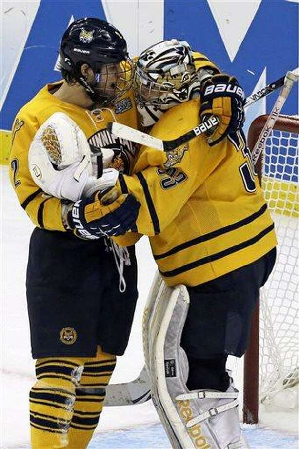Quinnipiac goalie Eric Hartzell (33) celebrates with defenseman Mike Dalhuisen (2) after a 4-1 win over St. Cloud State during of an NCAA college hockey Frozen Four semifinal game in Pittsburgh, Thursday, April 11, 2013. Quinnipaic advances to the national championship game Saturday against Yale. (AP Photo/Gene J. Puskar) Photo: ASSOCIATED PRESS / AP2013