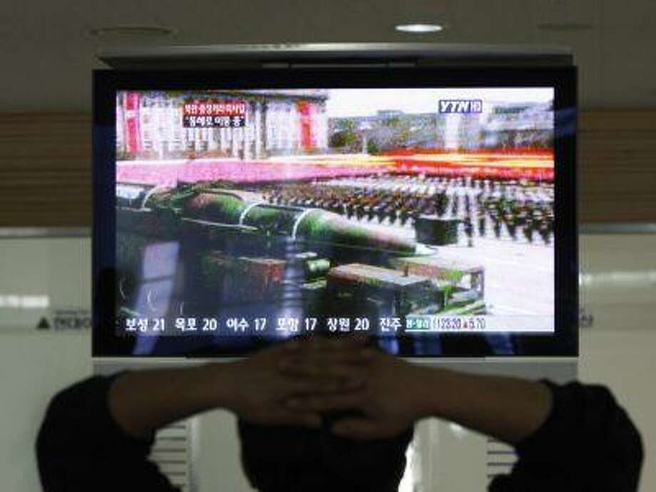 A South Korean man who is waiting to head to the North Korean city of Kaesong, watches a news program airing file footage of a North Korean rocket displayed during a military parade at the customs, immigration and quarantine office in Paju, South Korea, near the border village of Panmunjom, April 4. Photo: ASSOCIATED PRESS / AP2013