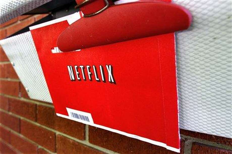 FILE - In this Thursday, Aug. 23, 2012, file photo, a Netflix envelop containing a DVD to be returned by mail is clipped onto a mailbox, in Springfield, Ill. Netflix won't miss Saturday mail delivery, even though the weekend service helped keep its DVD-by-mail subscribers happy. The U.S. Postal Service's planned shift to five days of home delivery a week instead of six may even make Netflix Inc. slightly more profitable. (AP Photo/Seth Perlman) Photo: AP / AP