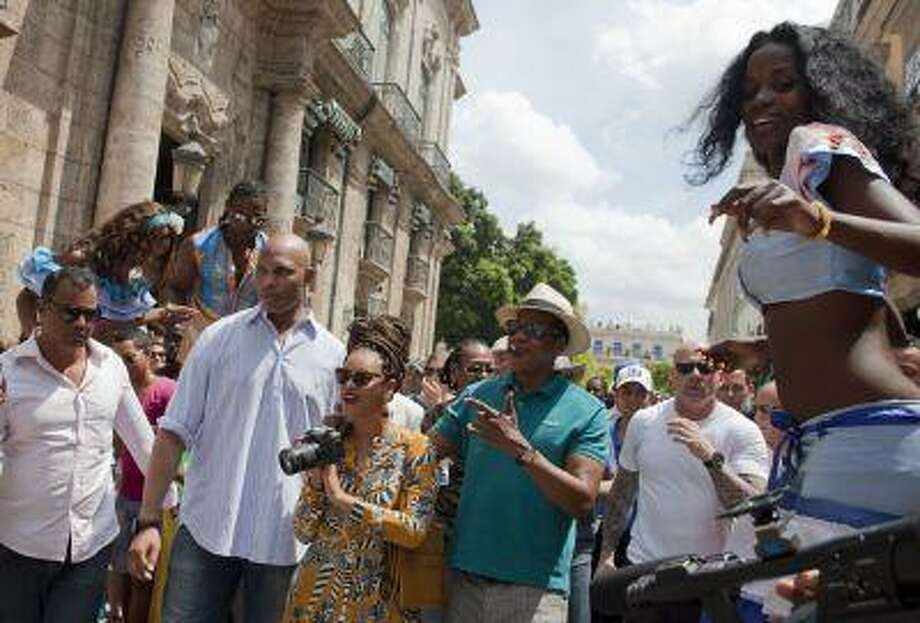 U.S. singer Beyonce and her husband, rapper Jay-Z, are surrounded by body guards as they tour Old Havana where a street performer on stilts looks on, right, in Cuba, Thursday, April 4, 2013. R&B's power couple is in Havana on their fifth wedding anniversary. (AP Photo/Ramon Espinosa) Photo: AP / AP