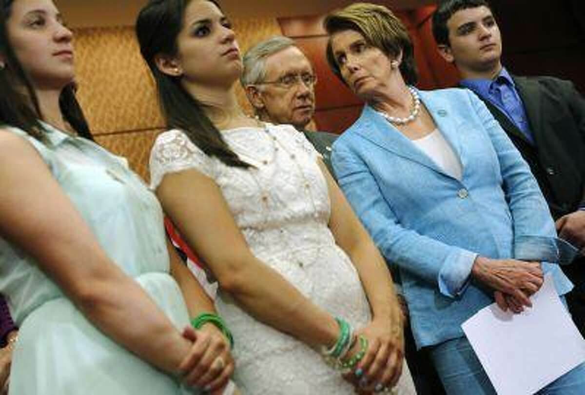 Senate Majority Leader Harry Reid, D., Nev., (center) and House Minority Leader Nancy Pelosi, D., Calif., (second from right) stand with Jillian Soto, Carlee Soto and Carlos Soto, siblings of slain Sandy Hook Elementary School teacher Victoria Soto, at a news conference about gun violence legislation on the six-month anniversary of the Connecticut shootings, at the U.S. Capitol in Washington, June 13, 2013.