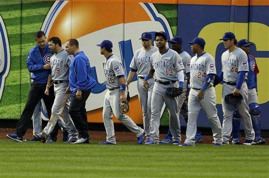 Chicago Cubs' David DeJesus (9) is helped off the field as teammates gather around him after he ran into the wall during the third inning of a baseball game against the New York Mets, Friday, June 14, 2013, in New York. (AP Photo/Frank Franklin II) Photo: AP / AP