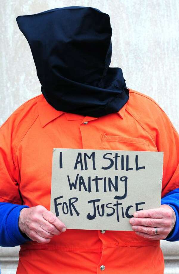 Jim Douglass of Birmingham, Alabama, protests the continued holding of prisoners at Guantanamo in front of the Federal Courthouse in New Haven on 4/11/2013.  He is dressed in an orange jumpsuit and a hood to represent the prisoners.Photo by Arnold Gold/New Haven Register