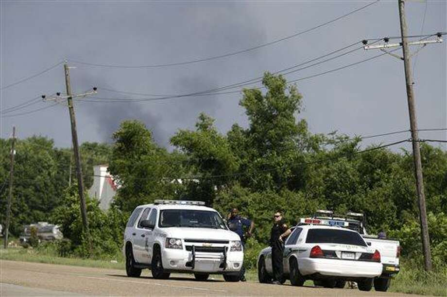 State police man a roadblock as smoke burns off from a flare at a chemical plant fire about twenty miles southeast of Baton Rouge, in Geismar, La., Thursday, June 13, 2013. The plant makes highly flammable gases that are basic building blocks in the petrochemical industry. (AP Photo/Gerald Herbert) Photo: AP / AP