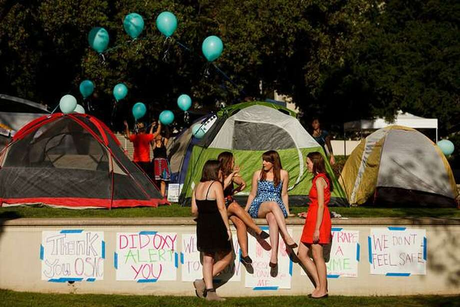 Students Carly Mee (blue) and Audrey Logan (red) talk with other students at the OSAC sexual assault awareness night campout at Occidental College in Los Angeles, California, U.S., on Friday, April 19, 2013. A group of students and faculty members has filed a complaint with the Education Department detailing violations of Title IX, the 1972 legislation that requires schools to maintain an environment equally welcoming to women and men, at Occidental. Photographer: Patrick Fallon/Bloomberg