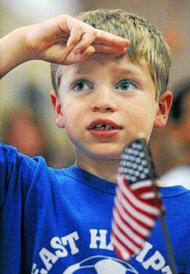 """Catherine Avalone/The Middletown Press Second grader Tommy Martin salutes the flag while singing the Star Stangled Banner during a Flag Day presentation by the VFW Post 5095 Ladies Auxiliary Friday afternoon at Memorial Elementary School in East Hampton. """"I brought  red, white and blue cupcakes to school today because it's my birthday tomorrow. I'm going to be eight,"""" said Martin. / TheMiddletownPress"""