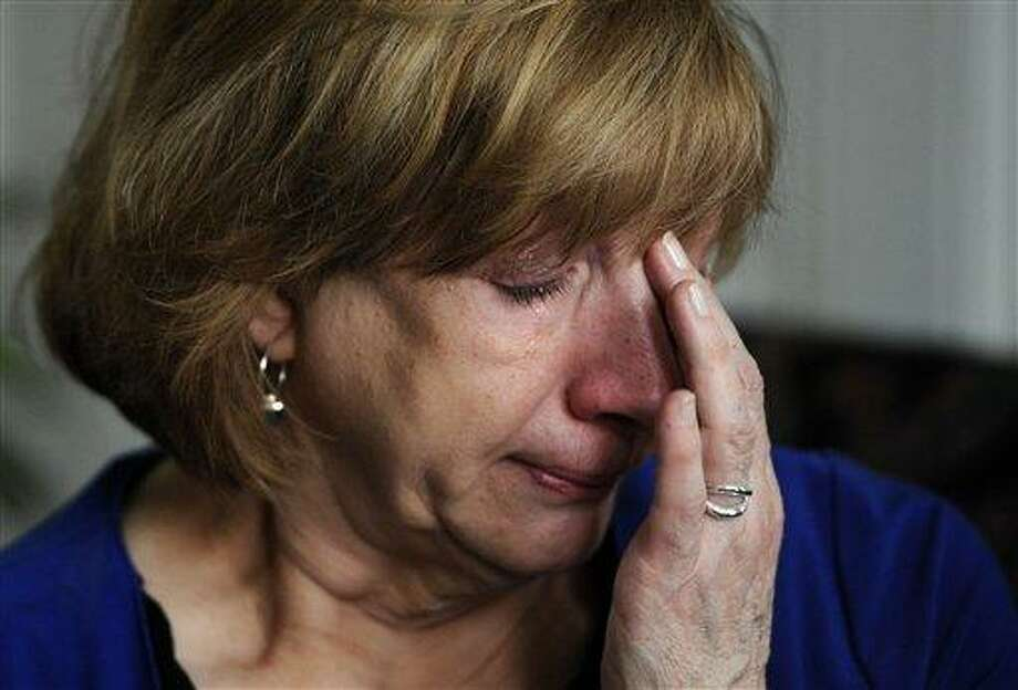 Teresa Rousseau wipes tears from her eyes while talking about her daughter Lauren Rousseau during an interview with the Associated Press at her home in Danbury, Conn., Tuesday, Feb. 5, 2013. Lauren Rousseau, 30, a teacher, was one of 26 people killed in the Dec. 14, 2012 massacre at Sandy Hook Elementary School in Newtown, Conn.  Lauren Rousseau will be one of six educators from the school honored posthumously with the 2012 Presidential Citizens Medal, presented at a White House ceremony on Feb. 15. (AP Photo/Jessica Hill) Photo: AP / FR125654 AP