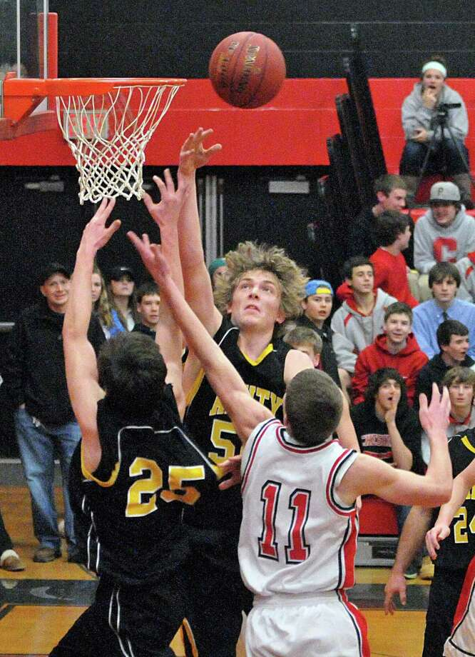 Amity's Remi Ferrell, center, and Dave Ryan try for the offensive rebound against Cheshire's Mark Dietrich during the first half of a recent game. Chesire fell to Wilby Wednesday. Photo-Peter Casolino/Register.