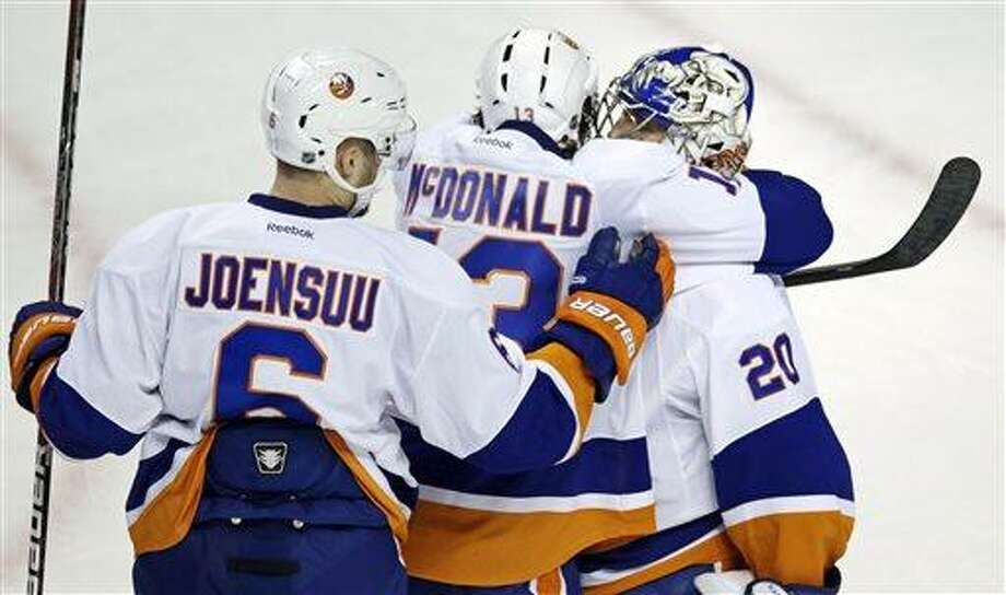 New York Islanders goalie Evgeni Nabokov (20) is congratulated by teammates Colin McDonald and Jesse Joensuu (6) after defeating the Boston Bruins 2-1 in an NHL hockey game in Boston, Thursday. (AP Photo/Charles Krupa) Photo: AP / AP