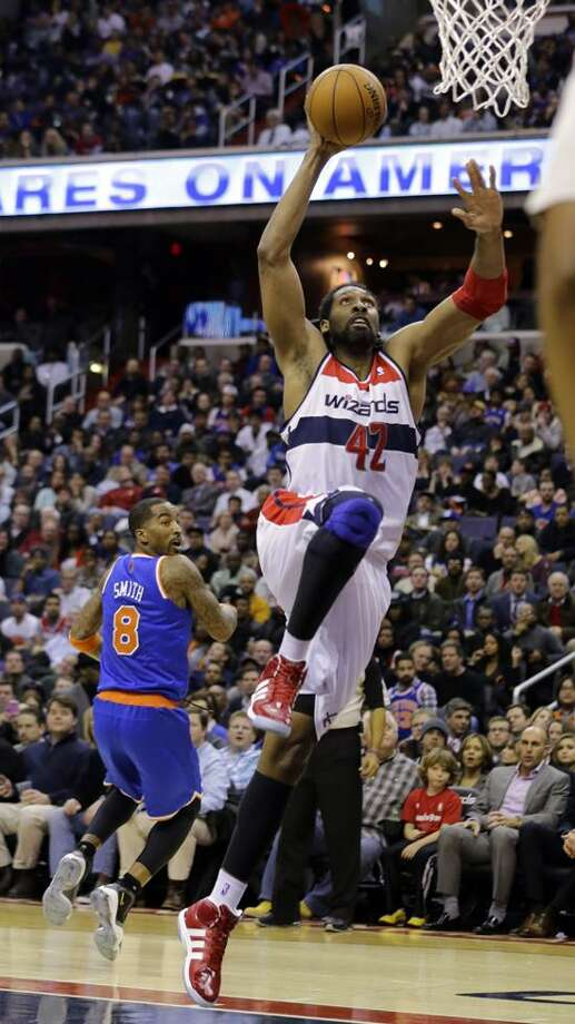 Washington Wizards center Nene (42), of Brazil, dunks as New York Knicks guard J.R. Smith (8) watches in the second half of an NBA basketball game, Wednesday, Feb. 6, 2013, in Washington. The Wizards won 106-96. (AP Photo/Alex Brandon) Photo: AP / AP