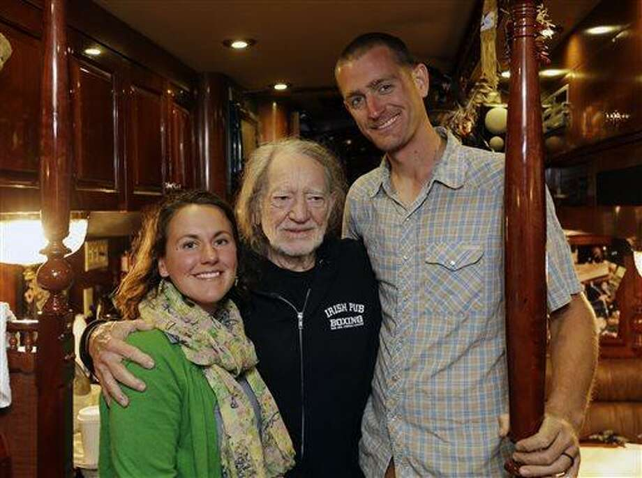 Country music artist Willie Nelson, center, poses with organic farmer Cara Fraver, left, and her husband Luke Deikis of Quincy Farm in Easton, N.Y., on his tour bus on Thursday, June 13, 2013, in Colonie, N.Y. Nelson is taking his annual Farm Aid benefit concert to upstate New York with an all-day festival of music and locally grown food in September. (AP Photo/Mike Groll) Photo: AP / AP