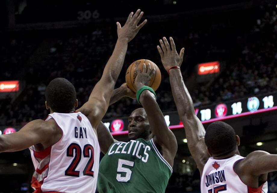 Boston Celtics forward Kevin Garnett (5) passes the ball under heavy pressure from Toronto Raptors forwards Rudy Gay (22) and Amir Johnson, right, during second-half NBA basketball game action in Toronto, Wednesday, Feb. 6, 2013. (AP Photo/The Canadian Press, Frank Gunn) Photo: AP / The Canadian Press