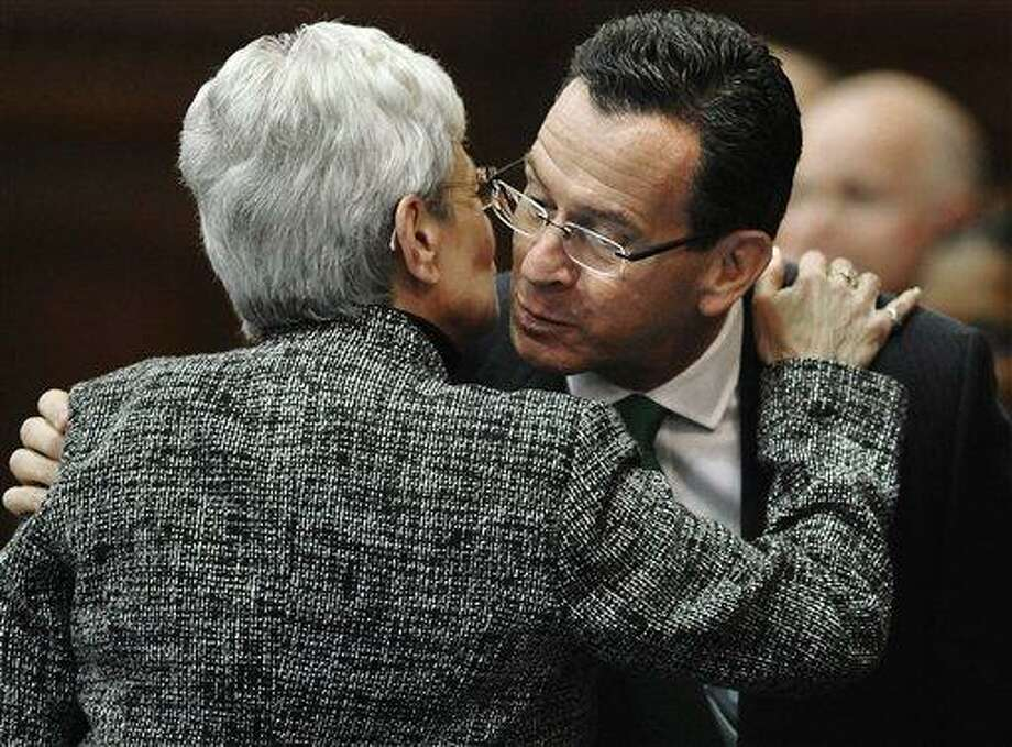 """Connecticut Gov. Dannel P. Malloy, right, is embraced by Lt. Gov. Nancy Wyman, after he is introduced for the State of the State address at the Capitol in Hartford, Conn., Wednesday, Jan. 9, 2013. Malloy urged state lawmakers Wednesday to work with him to prevent future tragedies like the Sandy Hook Elementary School shooting, but stressed that """"more guns are not the answer.""""  Legislators also must grapple with a projected deficit of about $1.2 billion. (AP Photo/Jessica Hill) Photo: AP / FR125654 AP"""
