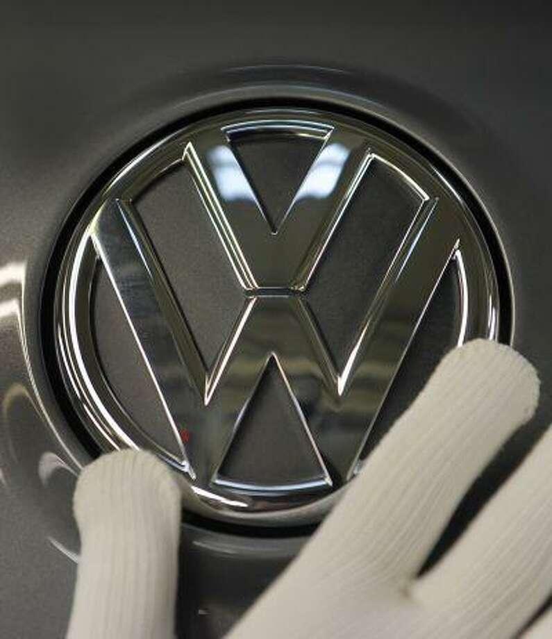 """ARCHIV - Ein Arbeiter montiert am 29. Oktober 2008 im Volkswagen-Werk in Zwickau das VW-Logo an einem Golf. Der insolvente Zulieferer Karmann hat laut einem Bericht einen millionenschweren Auftrag von VW erhalten und kann damit seine Transfergesellschaft fuer 1.540 gekuendigte Mitarbeiter finanzieren. Fuer den Entwicklungsauftrag in zweistelliger Millionenhoehe zahle VW Vorkasse und habe so die Gruendung der Transfergesellschaft ermoeglicht, berichtete die """"Neuen Osnabruecker Zeitung"""" am Freitag, 3. Juli 2009. (AP Photo/Eckehard Schulz) ** zu APD9716 ** -- FILE - An Oct 29, 2008 file picture shows a worker fixing a VW logo at a Golf VI at the assembly line of the Volkswagen plant in Zwickau, eastern Germany. (AP Photo/Eckehard Schulz) Photo: ASSOCIATED PRESS / AP2008"""