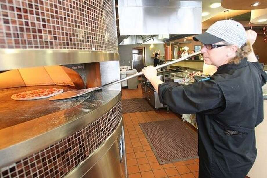 JOHN HAEGER @oneidaphoto on Twitter/Oneida Daily Dispatch Executive Chef Becca Dowsland checks on a pizza in the food court in the Students Actives Building at Morrisville State College in Morrisville on Wednesday, Feb. 6, 2013. Photo: Oneida Daily Dispatch / Oneida Daily Dispatch
