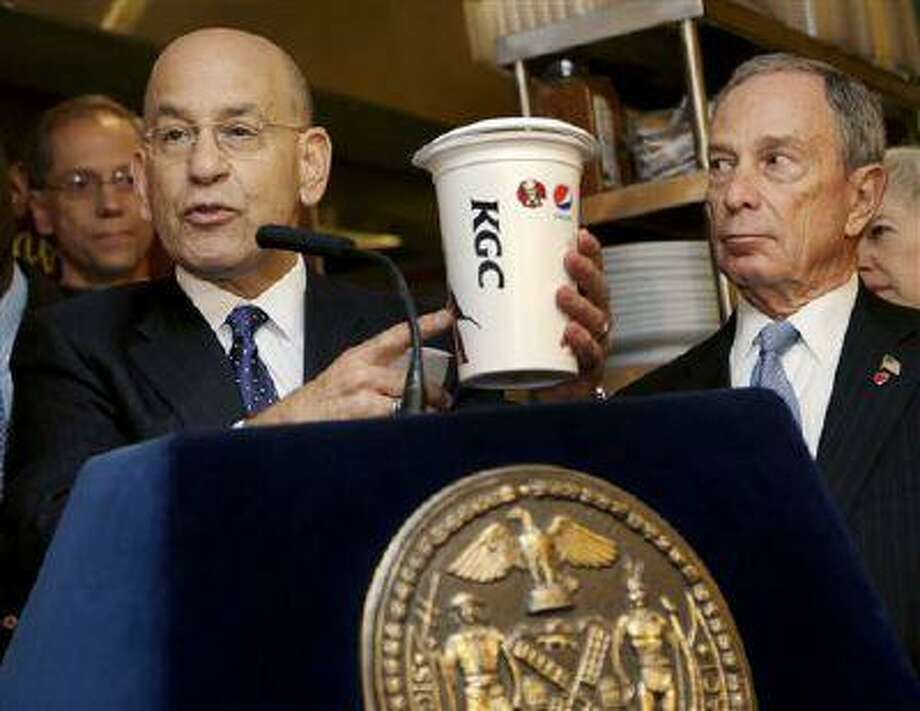 FILE- In this March 12, 2013 file photo, Montefiore Hospital President and CEO Steven Safyer, left, talks about large sugary drinks while New York City Mayor Michael Bloomberg looks on during a news conference at Lucky's Cafe in New York. A state appeals court panel peppered a city lawyer with tough questions during a Manhattan court session, Tuesday, June 11, 2013, aimed at determining whether New York City health officials exceeded their authority in placing a 16-ounce limit on most sweetened beverages at city-licensed eateries. (AP Photo/Seth Wenig, File) Photo: AP / AP
