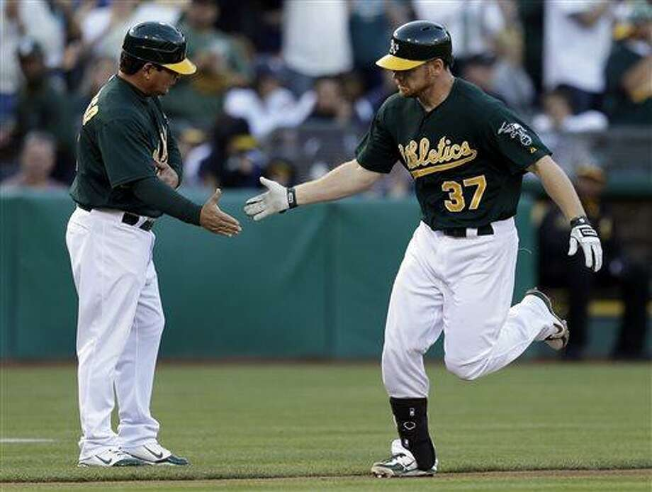 Oakland Athletics' Brandon Moss, right, is congratulated by third base coach Mike Gallego after hitting a two run home run off New York Yankees' Phil Hughes in the second inning of a baseball game on Wednesday, June 12, 2013, in Oakland, Calif. (AP Photo/Ben Margot) Photo: AP / AP