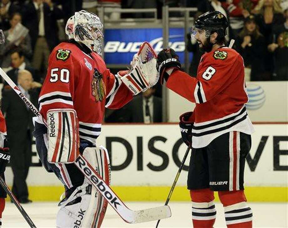 Chicago Blackhawks goalie Corey Crawford (50) celebrates with defenseman Nick Leddy (8) during the third overtime period of Game 1 in their NHL Stanley Cup Final hockey series, Thursday, June 13, 2013, in Chicago. (AP Photo/Nam Y. Huh) Photo: AP / AP