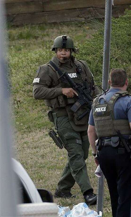 A police officer holds a rifle as he walks near the scene where a man was holding four Gwinnett County firefighters hostage in Suwanee, Ga., Wednesday, April 10, 2013. (AP Photo/John Bazemore) Photo: AP / AP
